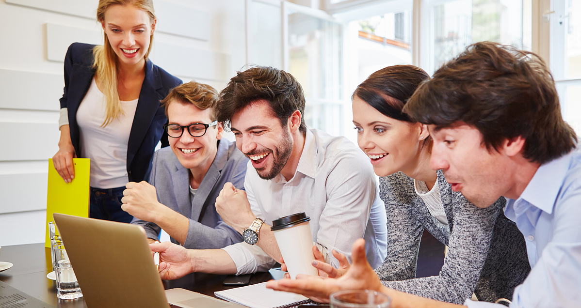 A happy team gathered around the computer for office training to represent employee productivity-1
