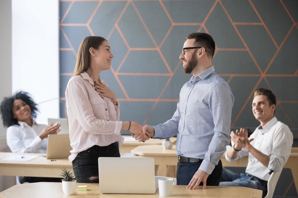 Boss handshaking successful female employee, demonstrating the importance of employee engagement