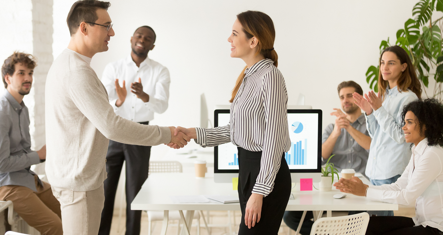 Boss shaking hand of an employee, surrounded by other employees applauding to represent employee rewards and recognition for employee productivity
