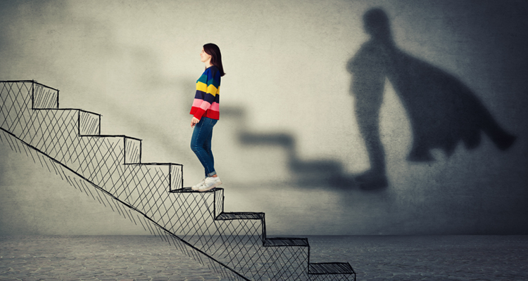 Employee climbing stairs and shadow of her with a superhero cape.