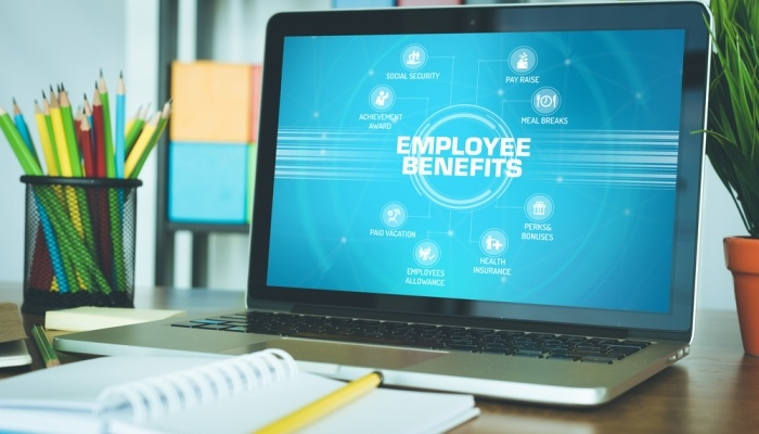 Laptop on office desk displaying types of employee benefits