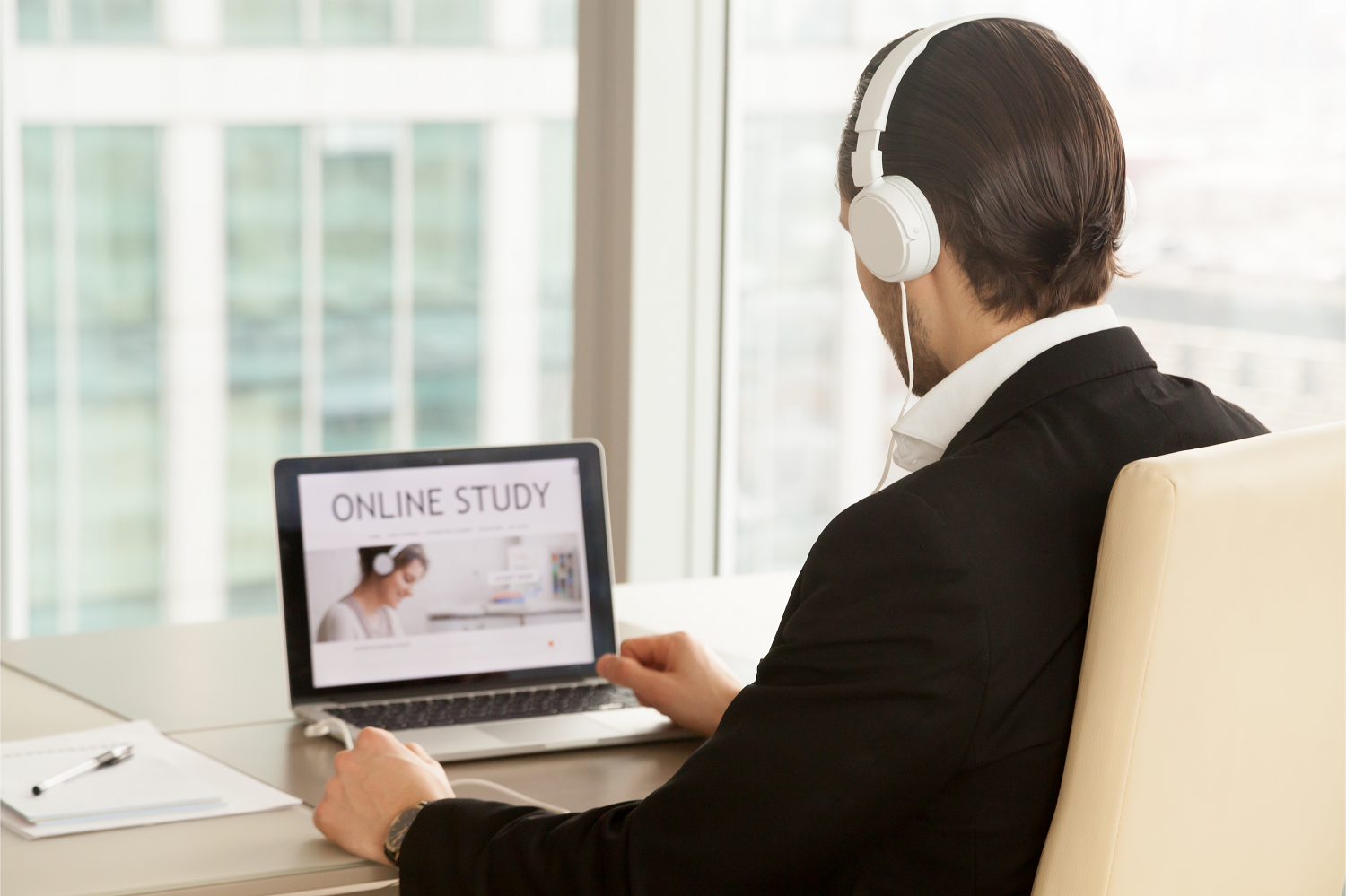 A man in headphones taking part in an online course on his laptop as part of his employer's staff engagement strategy.