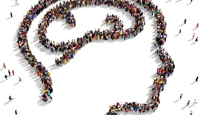 View from above at people standing together forming the shape of a head in order to draw attention to mental health