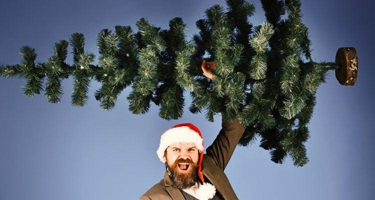 Employee wearing Christmas hat holding Christmas tree