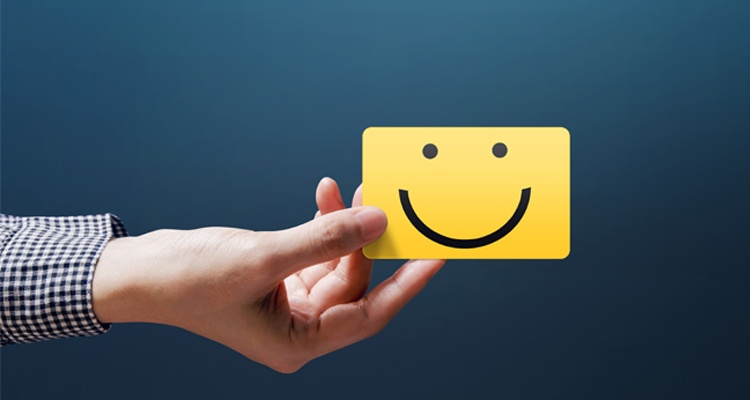 Happy employee holding a smile card