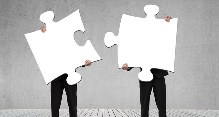 Two men holding puzzle pieces which fit together.