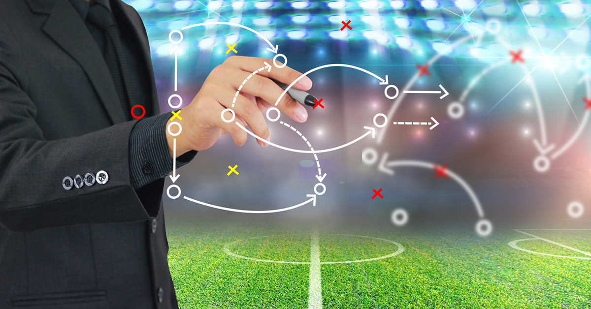 Man wearing a suit drawing a football strategy